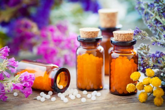 Pills in flask sorounded by herbs and spices
